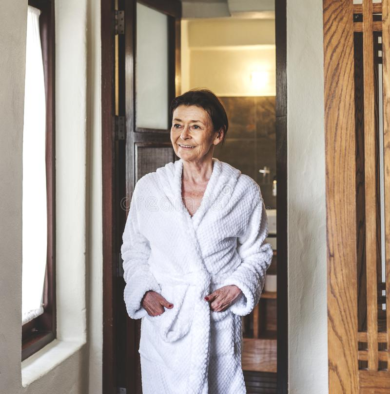 Mogen kvinna i en badrock på en semesterort royaltyfri foto