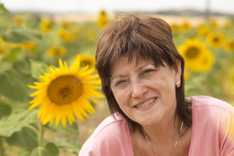 Mogen kvinna i ett fält av solrosor arkivbild
