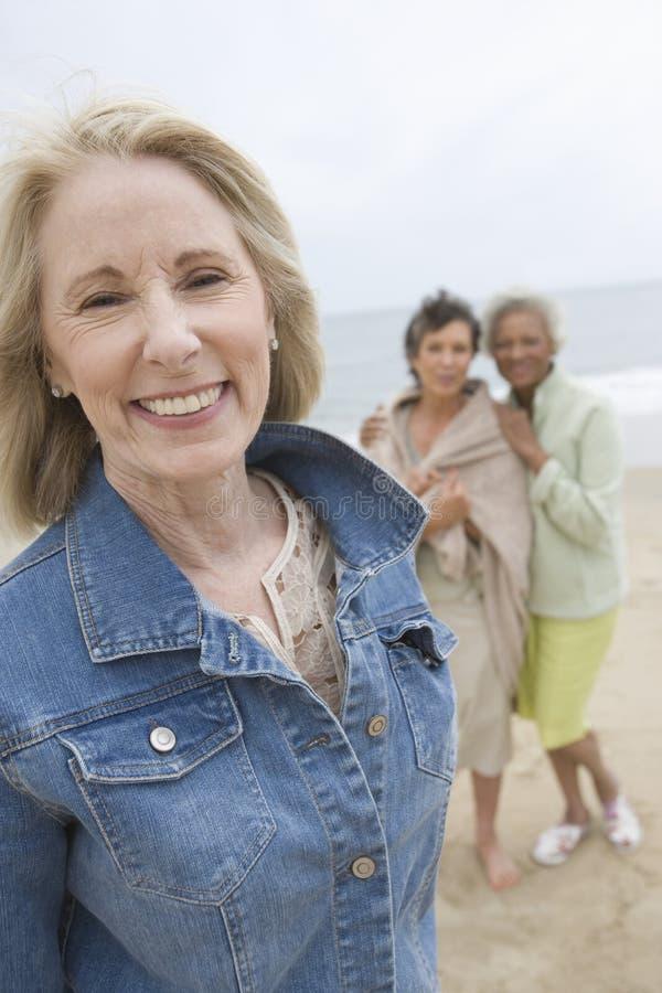Mogen kvinna i grov bomullstvillomslag på stranden med hennes vänner fotografering för bildbyråer