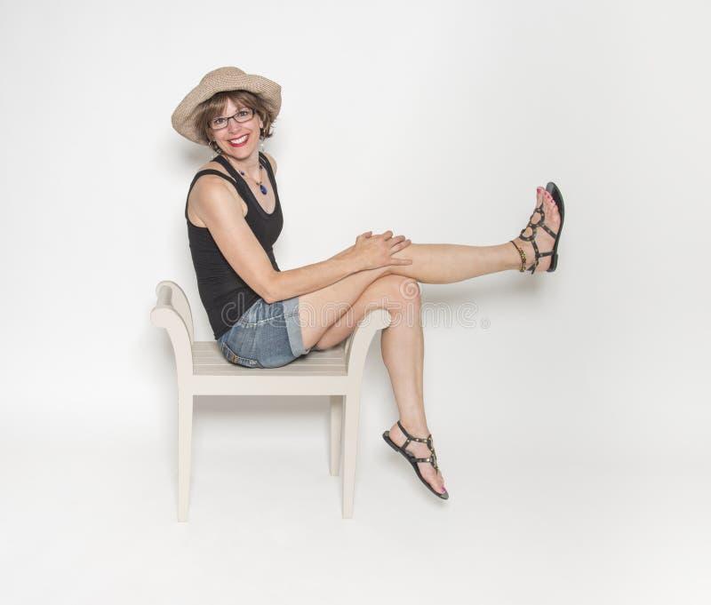 Mogen kvinna i hatten som poserar på stol royaltyfria foton