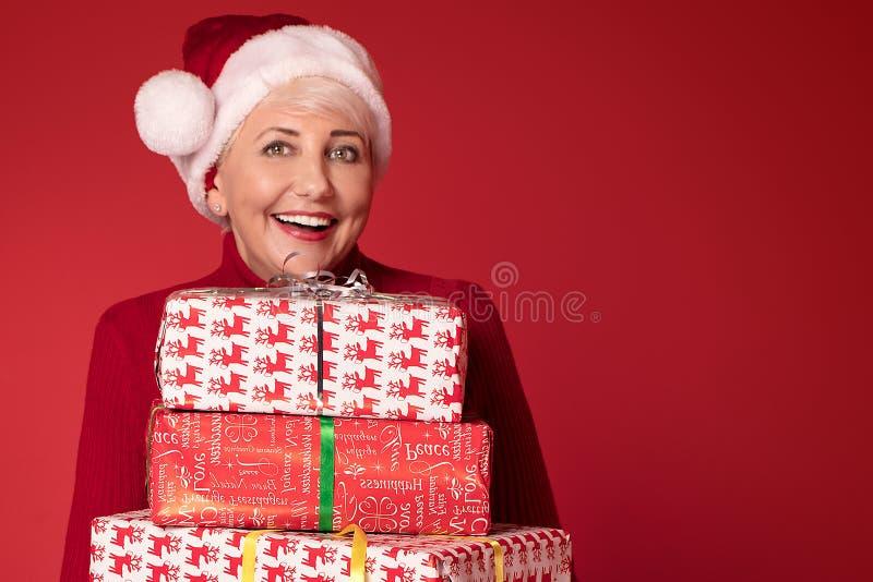 Mogen kvinna i röd bunt för Santa Claus hattinnehav av gåvaaskar, på röd studiobakgrund Julshopping, kopia fotografering för bildbyråer
