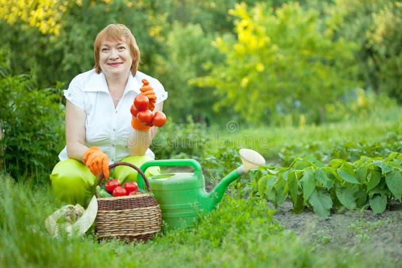 Mogen kvinna i trädgård royaltyfri fotografi