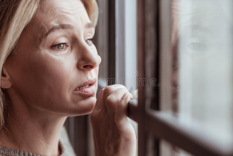 Mogen kvinna med ansikts- skrynklor som känner sig stressade och ledsna arkivbild