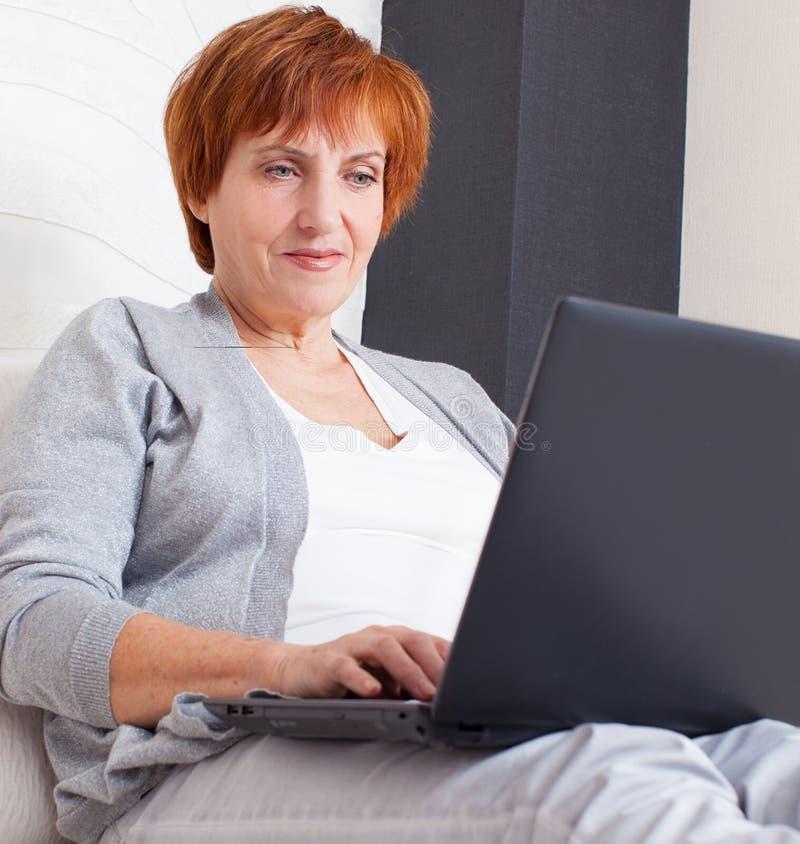 Mogen kvinna med bärbara datorn royaltyfria bilder