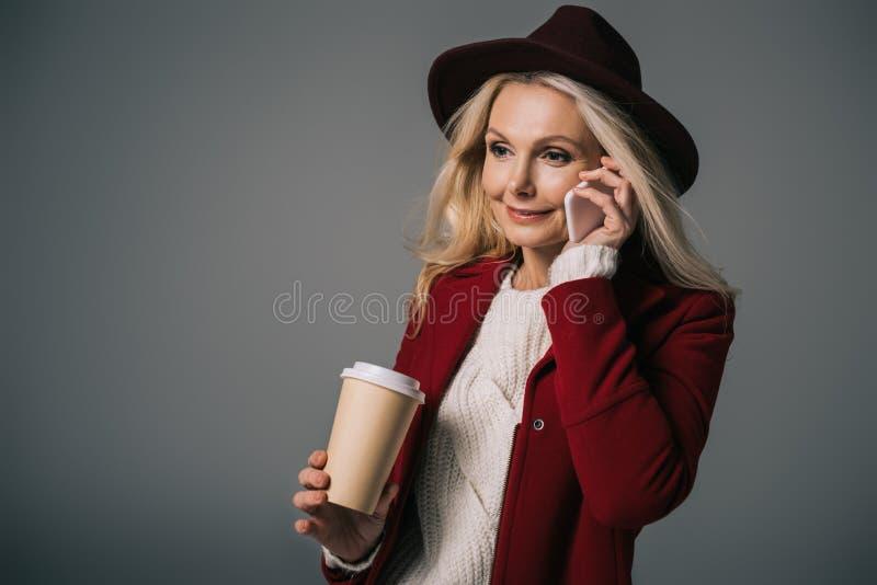 mogen kvinna med den pappers- koppen kaffe som talar vid telefonen royaltyfri foto