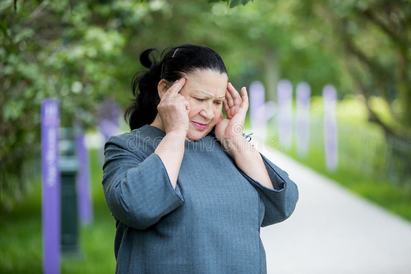 Mogen kvinna med en huvudvärk royaltyfri foto