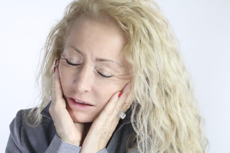 Mogen kvinna med en tandvärk arkivfoton