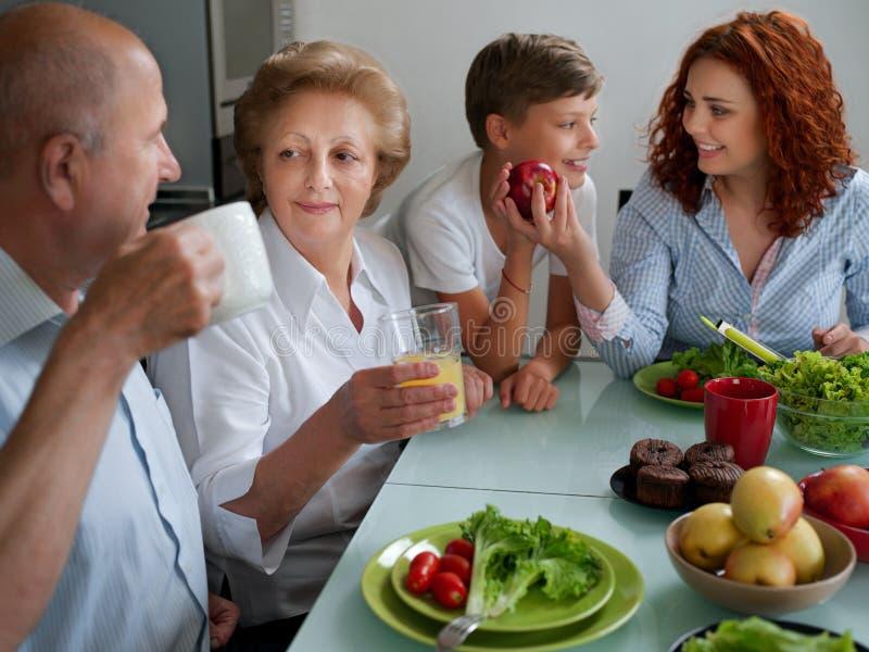 Mogen kvinna med familjmatställen på tabellen, hemmet, föräldrar, barn och morföräldrar, lycklig leendelunch fotografering för bildbyråer