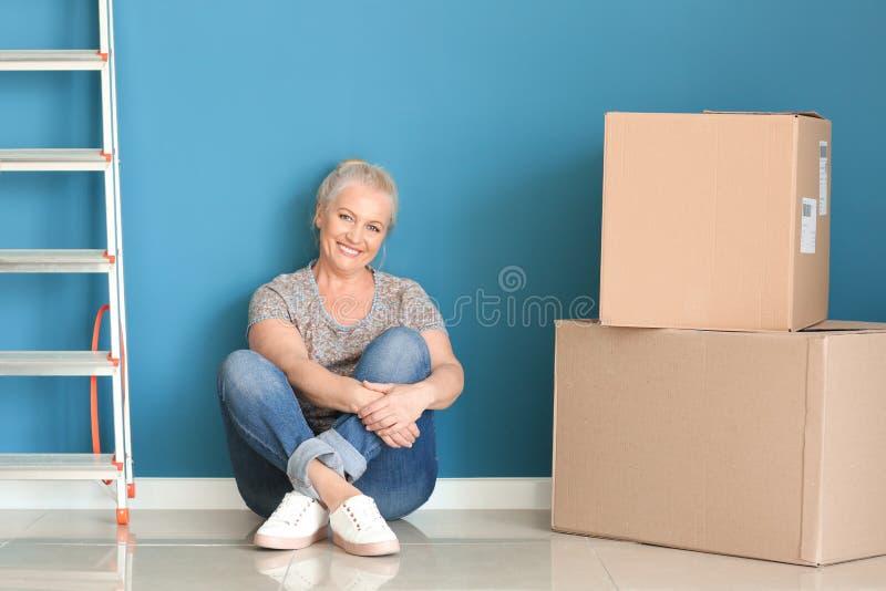 Mogen kvinna med flyttningaskar som sitter på golv på det nya hemmet arkivfoton