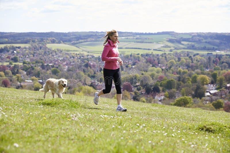 Mogen kvinna med golden retriever som joggar i bygd royaltyfri bild