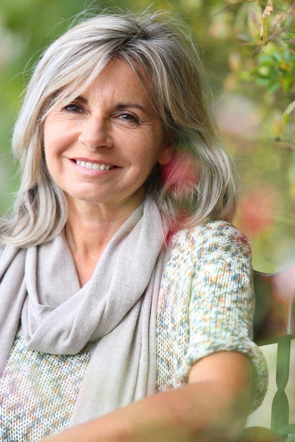 Mogen kvinna med grått sitta för hår som är utomhus- royaltyfria bilder