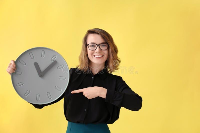 Mogen kvinna med klockan på färgbakgrund Begrepp f?r Tid ledning arkivfoto