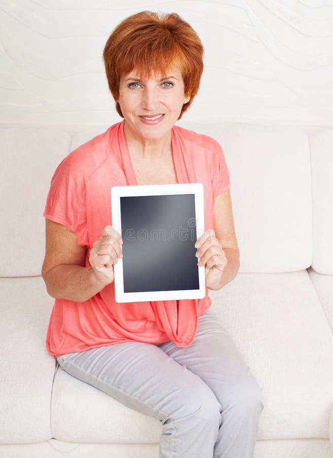 Mogen kvinna med minnestavlaPC arkivbild