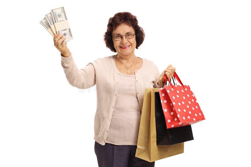 Mogen kvinna med packar av pengar- och shoppingpåsar arkivfoton