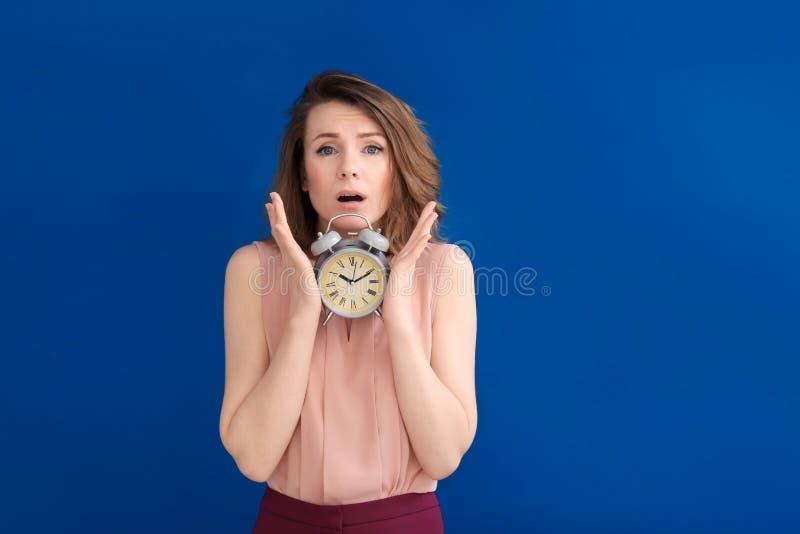 Mogen kvinna med ringklockan på färgbakgrund Begrepp f?r Tid ledning arkivfoto