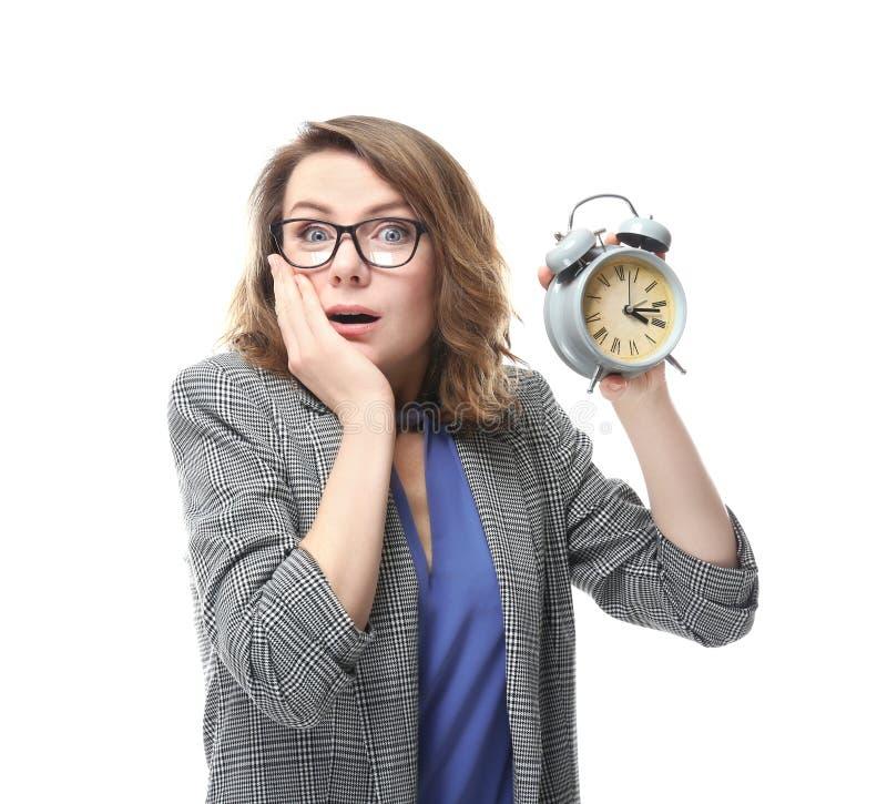 Mogen kvinna med ringklockan på vit bakgrund Begrepp f?r Tid ledning arkivfoto