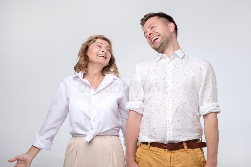 Mogen kvinna och man som fnissar på roligt skämt royaltyfria foton