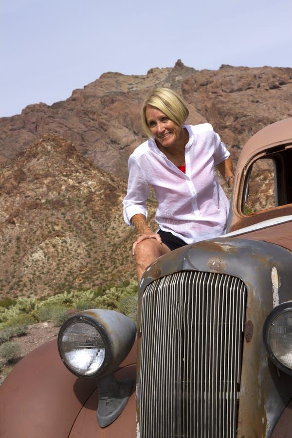 Mogen kvinna på den antika bilen i öknen arkivfoto