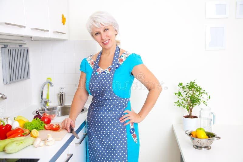 Mogen kvinna på kök arkivbild