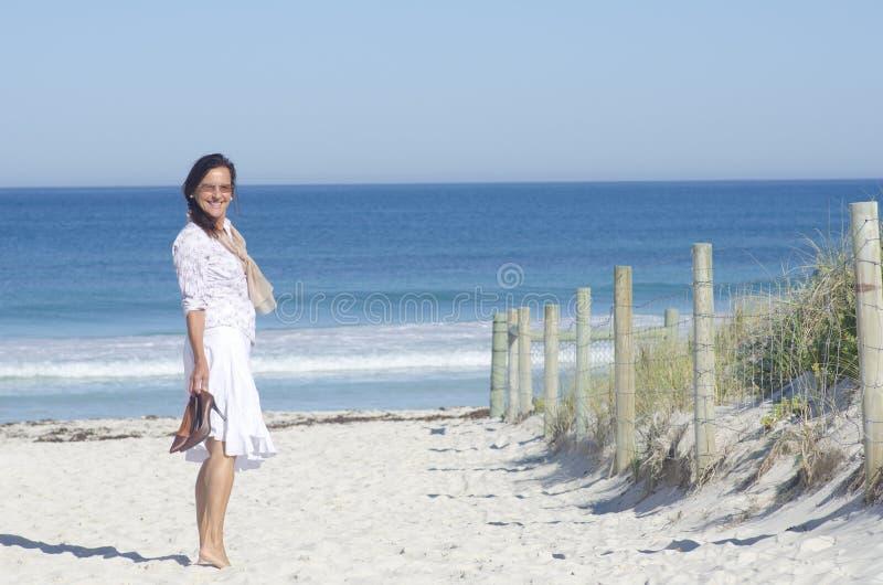 Mogen kvinna som är lycklig på stranden arkivfoto