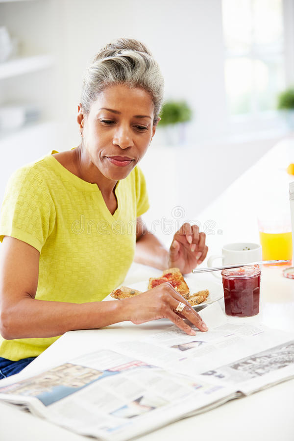 Mogen kvinna som äter frukosten och den läs- tidningen royaltyfri foto