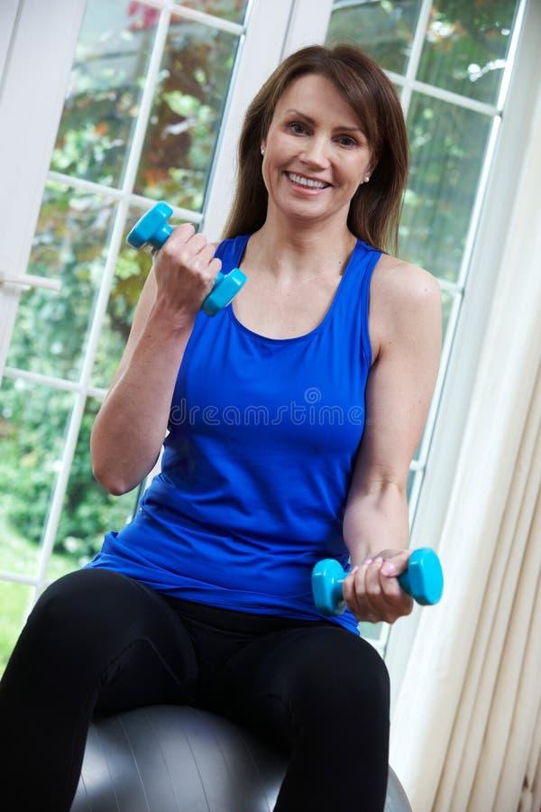 Mogen kvinna som övar med schweizarebollen och vikter hemma arkivfoto