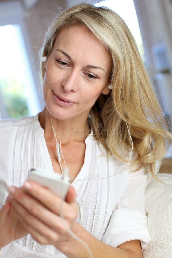 Mogen kvinna som använder hörlurar som talar på telefonen fotografering för bildbyråer