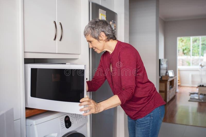Mogen kvinna som använder mikrovågugnen royaltyfri foto