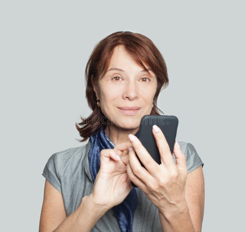 Mogen kvinna som använder smartphonen på vit arkivbilder