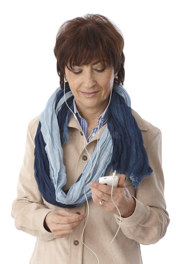Mogen kvinna som använder spelaren mp3 royaltyfri bild