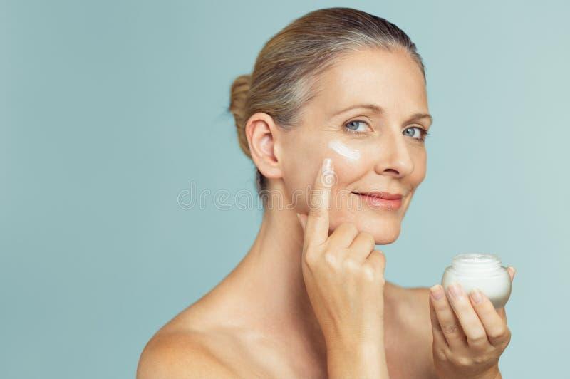 Mogen kvinna som applicerar hudkräm på framsida royaltyfria foton