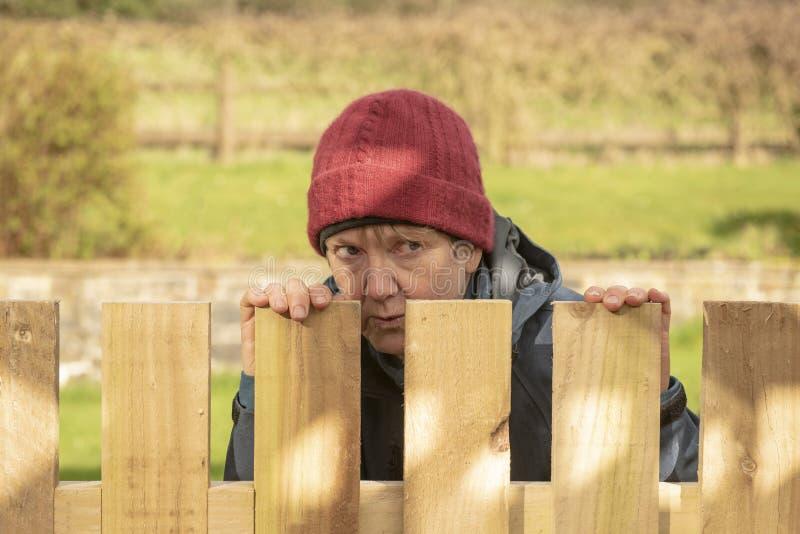Mogen kvinna som döljer bak staketet arkivbild