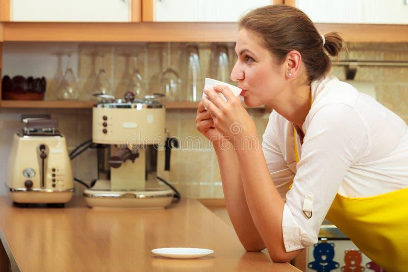 Mogen kvinna som dricker koppen kaffe i k?k royaltyfria foton