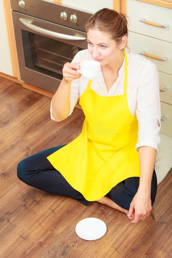 Mogen kvinna som dricker koppen kaffe i k?k arkivfoton