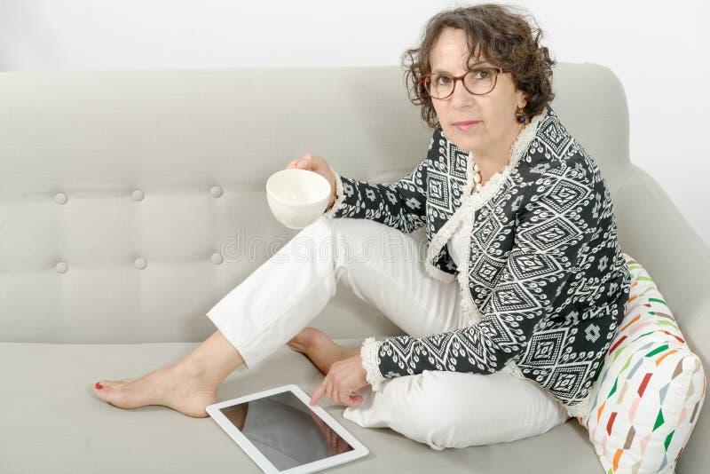 Mogen kvinna som dricker te på soffan arkivbild