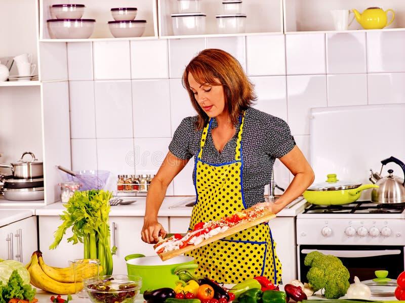 Mogen kvinna som förbereder sig på kök royaltyfri foto