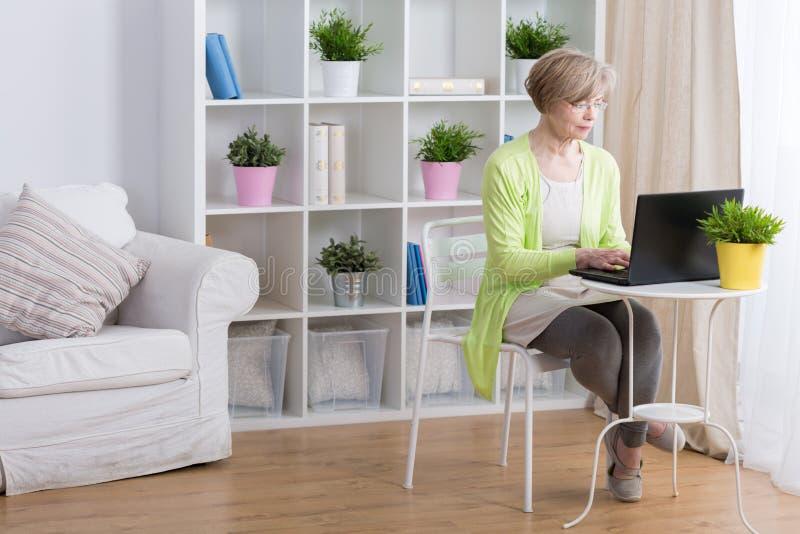 Mogen kvinna som fungerar på bärbar dator arkivbild