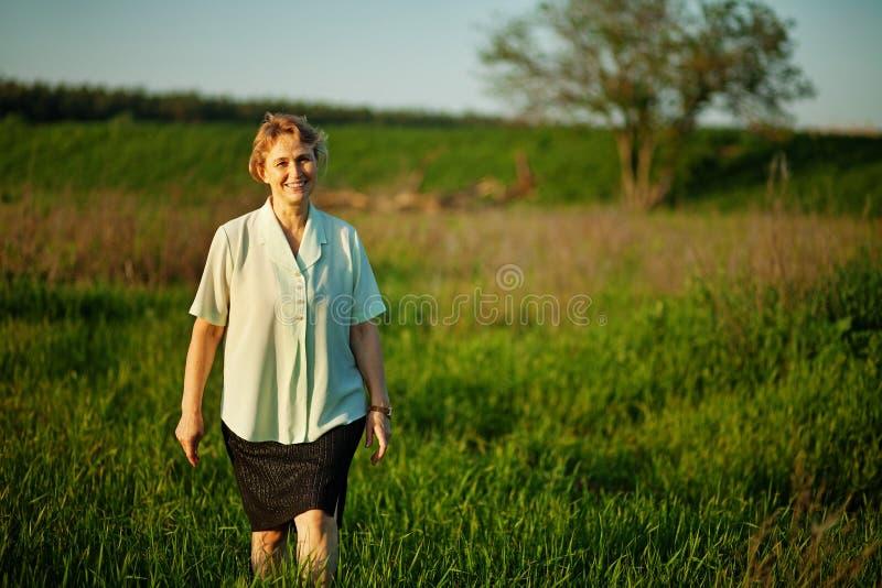Mogen kvinna som går i ett fält royaltyfri bild