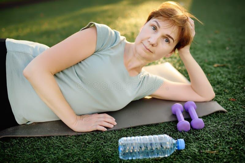 Mogen kvinna som gör konditionövning med hantlar arkivfoton
