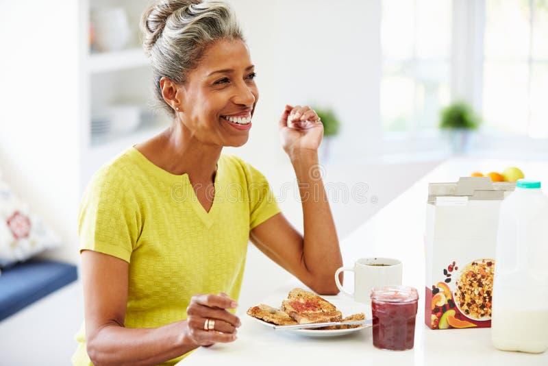 Mogen kvinna som hemma äter frukosten arkivbilder