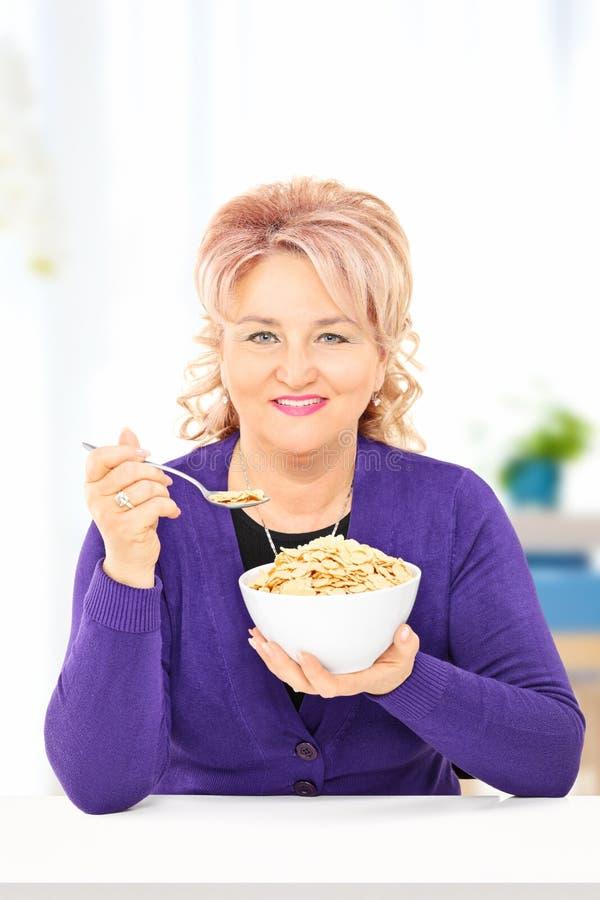 Mogen kvinna som hemma äter sädesslag på en tabell arkivfoton
