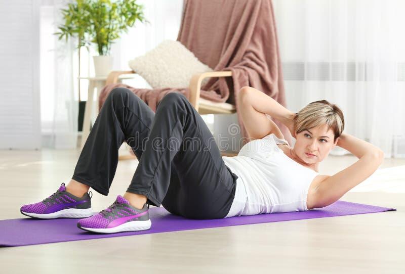 Mogen kvinna som hemma gör sitta-UPS arkivfoto