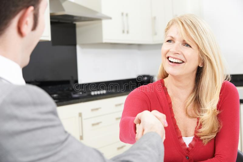 Mogen kvinna som hemma skakar händer med den finansiella rådgivaren arkivfoto