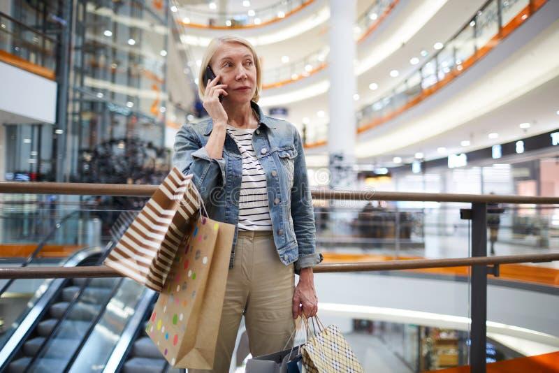 Mogen kvinna som kallar vännen i shoppinggalleria fotografering för bildbyråer