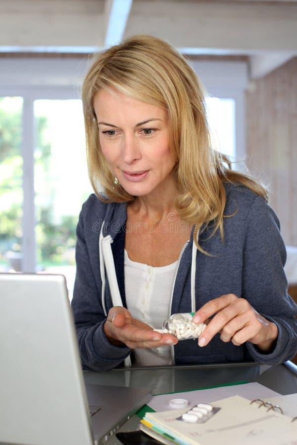 Mogen kvinna som kontrollerar medicinanvändning på bärbara datorn arkivbilder