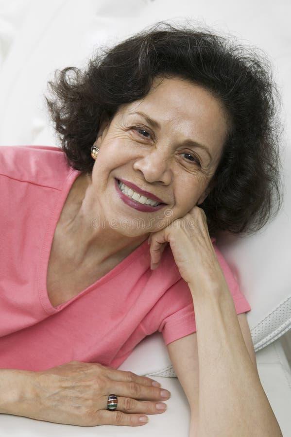 Mogen kvinna som kopplar av på soffan royaltyfria foton