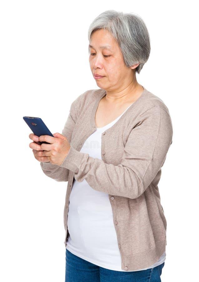 Mogen kvinna som läs på mobiltelefonen royaltyfria bilder