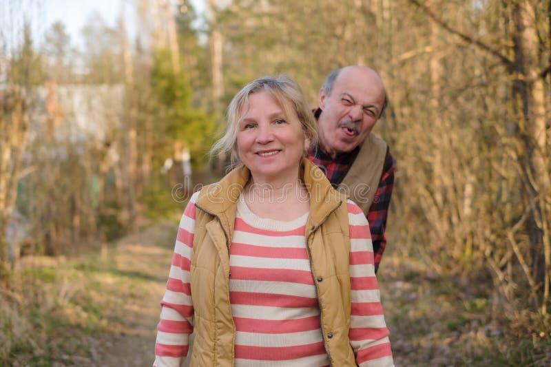 Mogen kvinna som ler det utomhus- anseendet Hennes make som retar hennes visande tunga arkivfoton