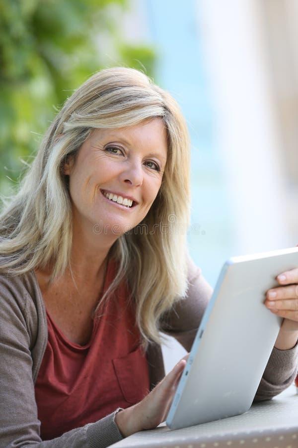 Mogen kvinna som ler genom att använda minnestavlan royaltyfria bilder