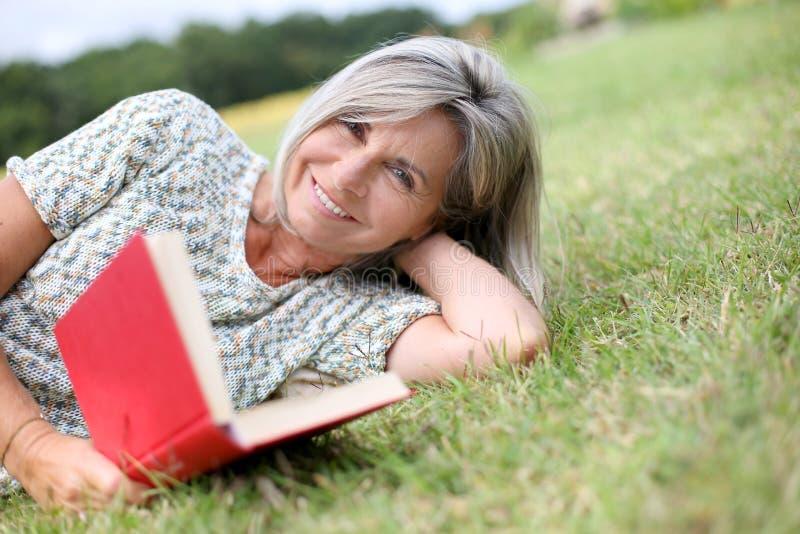 Mogen kvinna som ligger i gräsläsebok royaltyfria foton